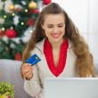 Happy young woman near Christmas tree making online purchases — Stock Photo