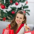 Happy young woman near Christmas tree with shopping bags — Stock Photo