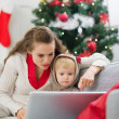 Mother showing baby something in laptop near Christmas tree — Stock Photo