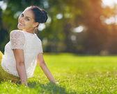 Porträtt av glad tjej sitter på ängen — Stockfoto