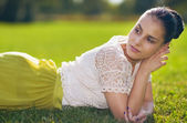 Thoughtful young woman laying on grass — Stock Photo