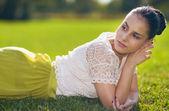 Pensativa jovem mulher deitada na grama — Foto Stock