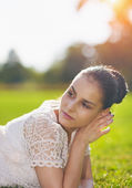 Thoughtful girl laying on grass — Stockfoto