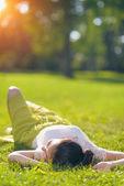 Junge frau auf der wiese entspannen. rückansicht — Stockfoto