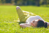 Young woman relaxing on grass. Rear view — Stock Photo
