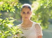 Portrait of young woman standing in foliage — Stock Photo