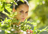 Portrait of girl hiding in foliage — Stock Photo