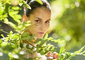 Portrait of girl hiding in foliage — Stock Photo