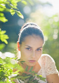 Portrait of young woman in foliage — Stock Photo