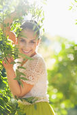 Smiling young woman playing in foliage — Stock Photo