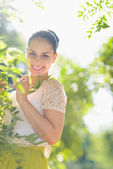Smiling girl playing in foliage — Stock Photo
