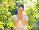 Young woman holding seed in palms in forest — Stock Photo