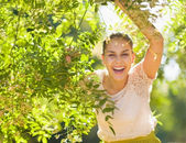 Smiling young woman looking out from foliage — Stock Photo
