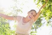 Glad flicka som leker i bladverk i skogen — Stockfoto