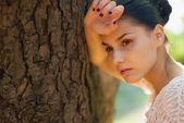 思いやりのある女の子の木にもたれる — ストック写真