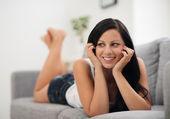 ソファの上に敷設、コピー上で探して幸せの若い女性の肖像画 — ストック写真