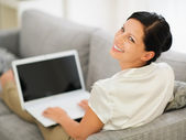Smiling young woman laying on couch and working on laptop — Stock Photo