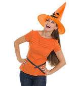 Curious young woman in Halloween hat looking on copy space — Stock Photo