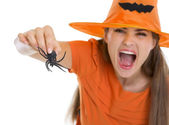 Woman in Halloween hat scaring with spider — Stock Photo