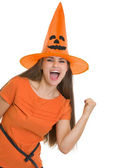 Happy young woman in Halloween hat showing yes gesture — Stock Photo