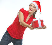 Cheerful young woman presenting Christmas gift box — Stock Photo
