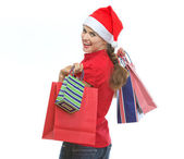 Young woman in Christmas hat with shopping bags looking out — Stock Photo