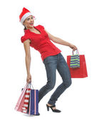 Happy young woman in Santa hat holding heavy shopping bags — Stock Photo