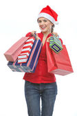 Happy young woman in Santa hat holding shopping bags — Stock Photo