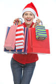 Happy young woman in Christmas hat with shopping bags — Stock Photo