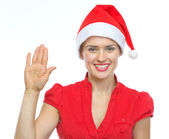Happy young woman in Christmas hat saluting — Stock Photo