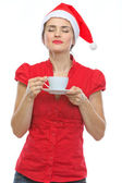 Young woman in Christmas hat enjoying cup of coffee — Stock Photo