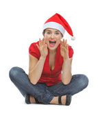 Young woman in Christmas hat shouting through megaphone shaped h — Stock Photo