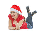 Happy young woman with Christmas hat laying on floor and pointin — Stock Photo