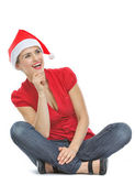 Happy young woman with Christmas hat sitting on floor and lookin — Stock Photo