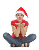 Happy young woman with Christmas hat sitting on floor and blowin — Stock Photo