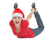 Cheerful young woman with Christmas hat laying on floor — Stock Photo