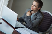 Thoughtful business woman sitting at desk in hotel room — Stock Photo