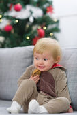 Scared baby in Christmas deer suit with cookie — Stock Photo