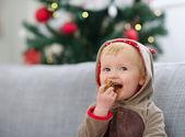 Happy Baby auf Weihnachten Anzug Essen cookie — Stockfoto