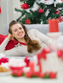 Happy young woman laying on couch near Christmas tree — Stock Photo