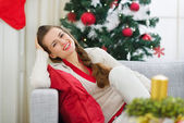Portrait of happy young woman near Christmas tree — Stock Photo