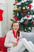 Glückliche junge frau in der nähe von weihnachtsbaum-lesung-postkarte — Stockfoto