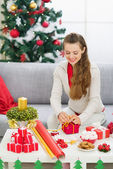 Happy young woman preparing Christmas gift — Stock Photo