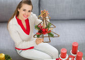 Smiling young woman showing Christmas decorations — Stock Photo