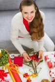 Mujer joven sonriente haciendo adornos navideños — Foto de Stock