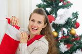 Smiling young woman checking Christmas socks — Stock Photo