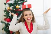 Smiling young woman balancing Christmas present box on head — Stock Photo