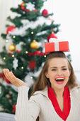 Happy young woman balancing Christmas present box on head — Stock Photo