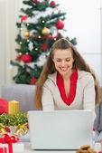 Mulher jovem feliz perto de árvore de natal usando laptop — Foto Stock