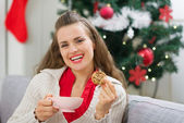 Happy young woman near Christmas tree with cup and cookie — Stock Photo